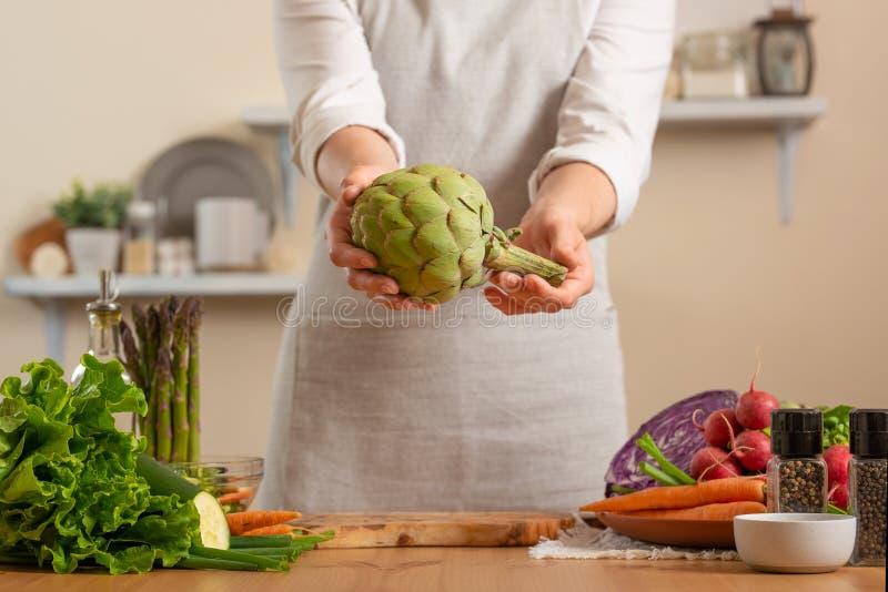 Cozinheiro chefe que prepara a alcachofra O conceito do alimento saudável e integral de perda, desintoxicação, vegetariano que co imagem de stock