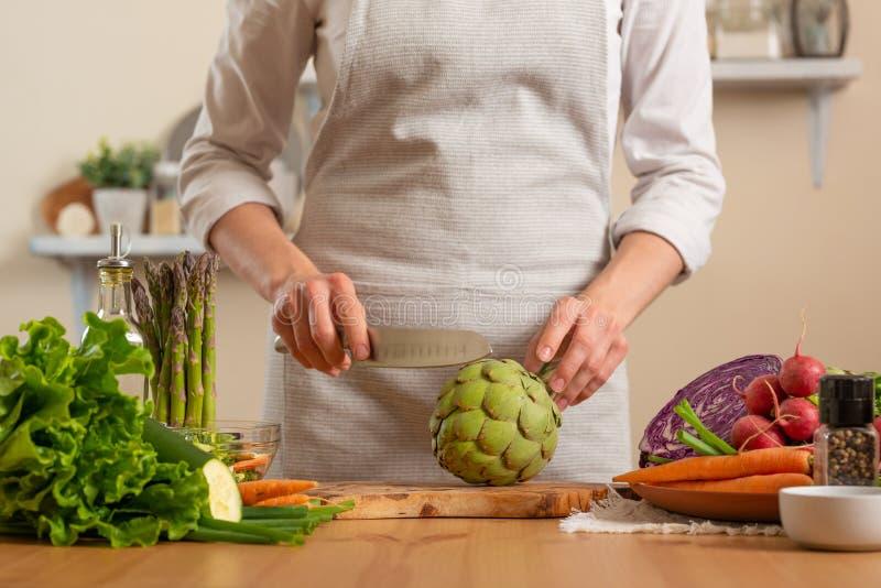 Cozinheiro chefe que prepara a alcachofra O conceito do alimento saudável e integral de perda, desintoxicação, vegetariano que co fotos de stock