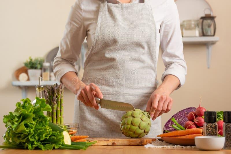 Cozinheiro chefe que prepara a alcachofra O conceito do alimento saudável e integral de perda, desintoxicação, vegetariano que co fotografia de stock royalty free