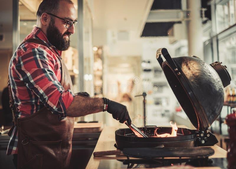 Cozinheiro chefe que prepara carvões vegetais antes de grelhar em um restaurante foto de stock royalty free