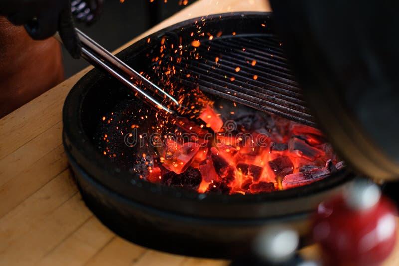 Cozinheiro chefe que prepara carvões vegetais antes de grelhar em um restaurante fotos de stock