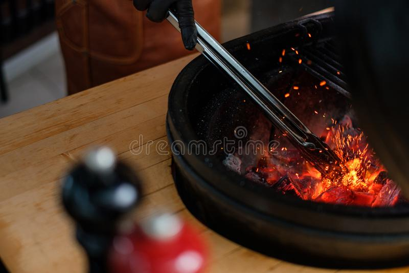 Cozinheiro chefe que prepara carvões vegetais antes de grelhar em um restaurante fotografia de stock
