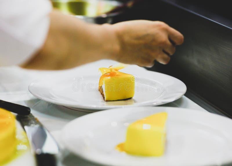 Cozinheiro chefe que prepara o alimento, refeição na cozinha, cozinheiro chefe que cozinha, cozinheiro chefe que decora o prato,  foto de stock