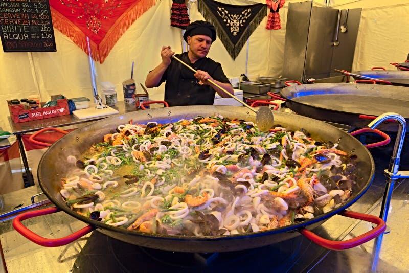 Cozinheiro chefe que prepara o paella fotografia de stock