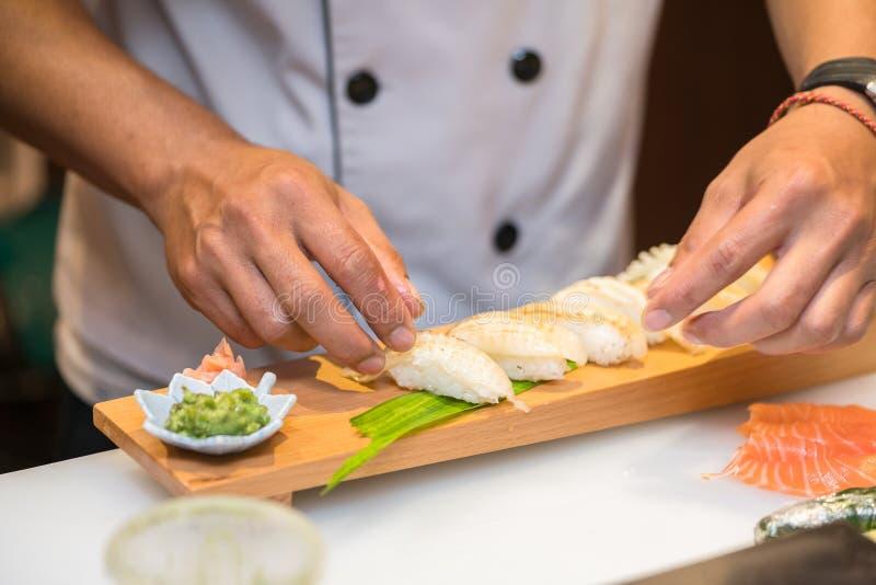 Cozinheiro chefe que prepara o sushi na cozinha do restaurante imagens de stock