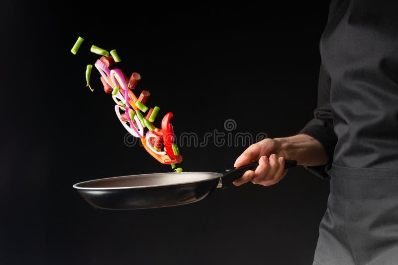 Cozinheiro chefe que prepara salsichas dos pepperoni com feijões verdes, pimentas de sino doce e anéis de cebola vermelha, em um  imagens de stock royalty free