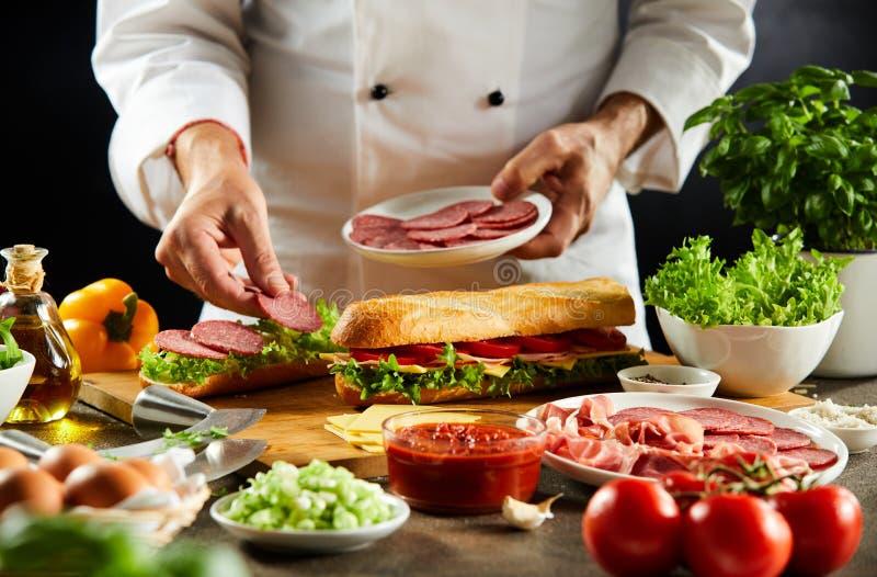 Cozinheiro chefe que prepara um sanduíche duro do baguette fotos de stock