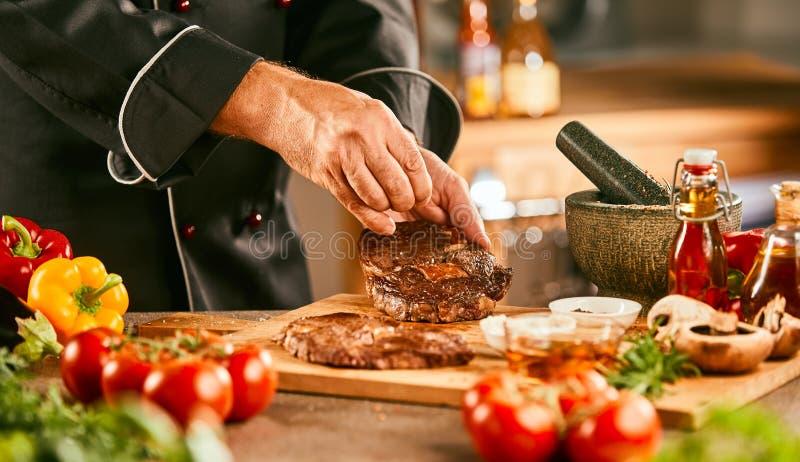 Cozinheiro chefe que tempera um bife cru para grelhar imagem de stock