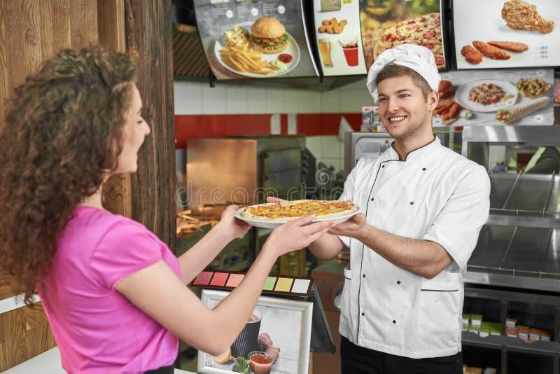 Cozinheiro chefe que trabalha na pizaria e que propõe a pizza à menina bonita imagens de stock royalty free