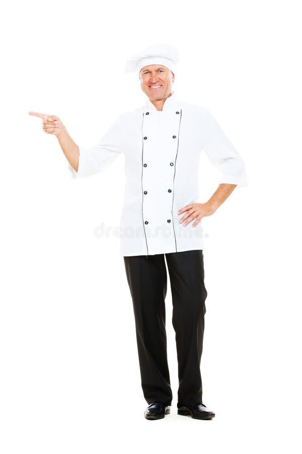 Cozinheiro chefe sênior do smiley que aponta em algo imagens de stock royalty free