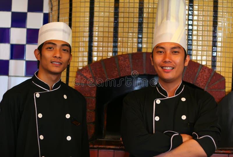Cozinheiro chefe sênior e júnior imagens de stock