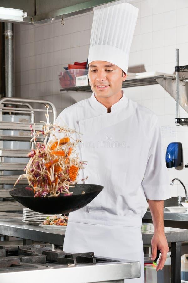 Cozinheiro chefe Tossing Vegetables no frigideira chinesa fotos de stock royalty free