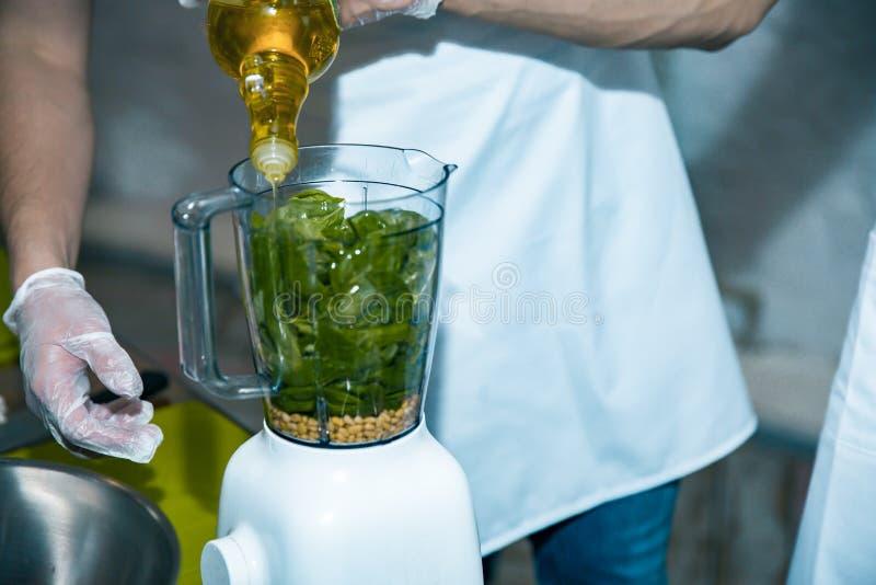 Cozinheiro chefe vegetal do batido que mistura batidos verdes com a casa do misturador na cozinha Retrato saudável do conceito do imagem de stock