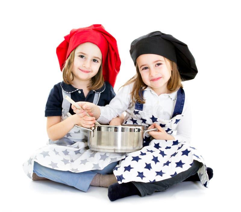 Cozinheiro da irmã das crianças dos gêmeos com potenciômetro imagem de stock