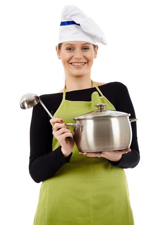 Cozinheiro da jovem mulher com a concha do potenciômetro e de sopa imagem de stock