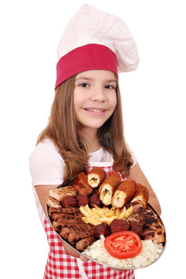 Cozinheiro da menina com carne e salada grelhadas misturadas na placa fotos de stock royalty free