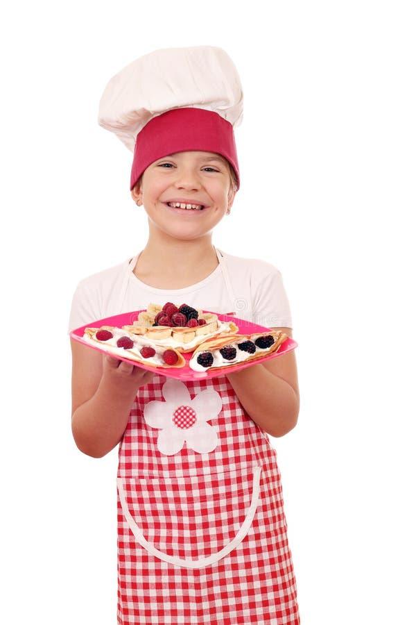 Cozinheiro da menina com os crepes e frutos doces deliciosos imagens de stock royalty free