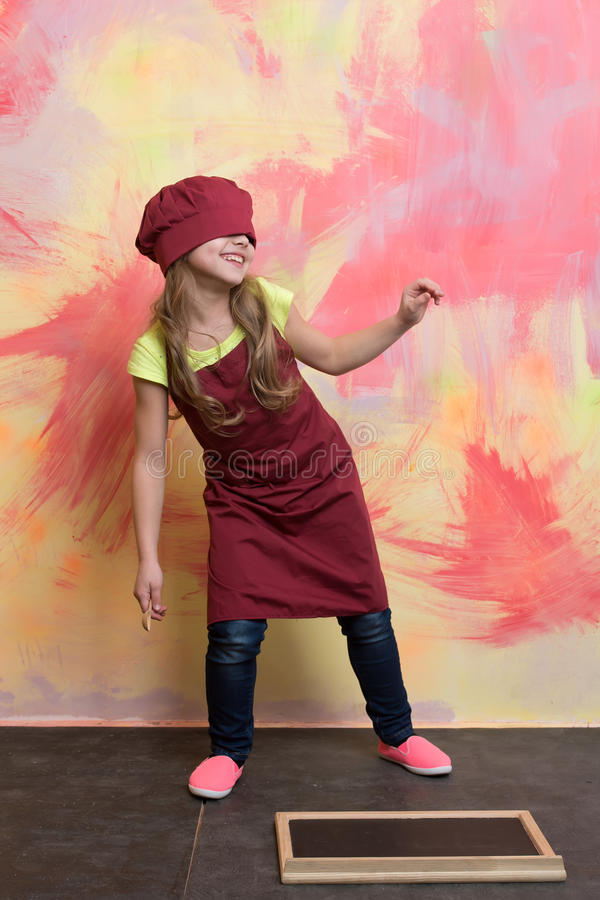 Cozinheiro da menina que tem o divertimento no chapéu e no avental do cozinheiro chefe fotos de stock royalty free