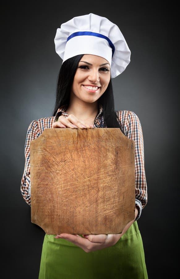 Cozinheiro da mulher que guarda uma placa com copyspace fotos de stock royalty free