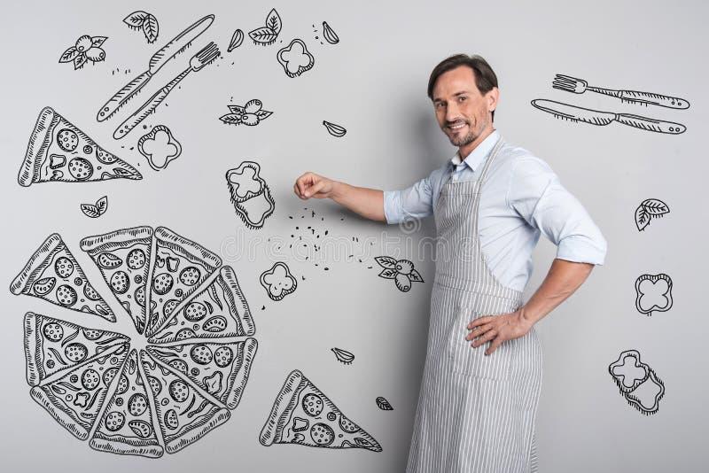 Cozinheiro de sorriso que adiciona especiarias ao cozinhar a pizza fotos de stock