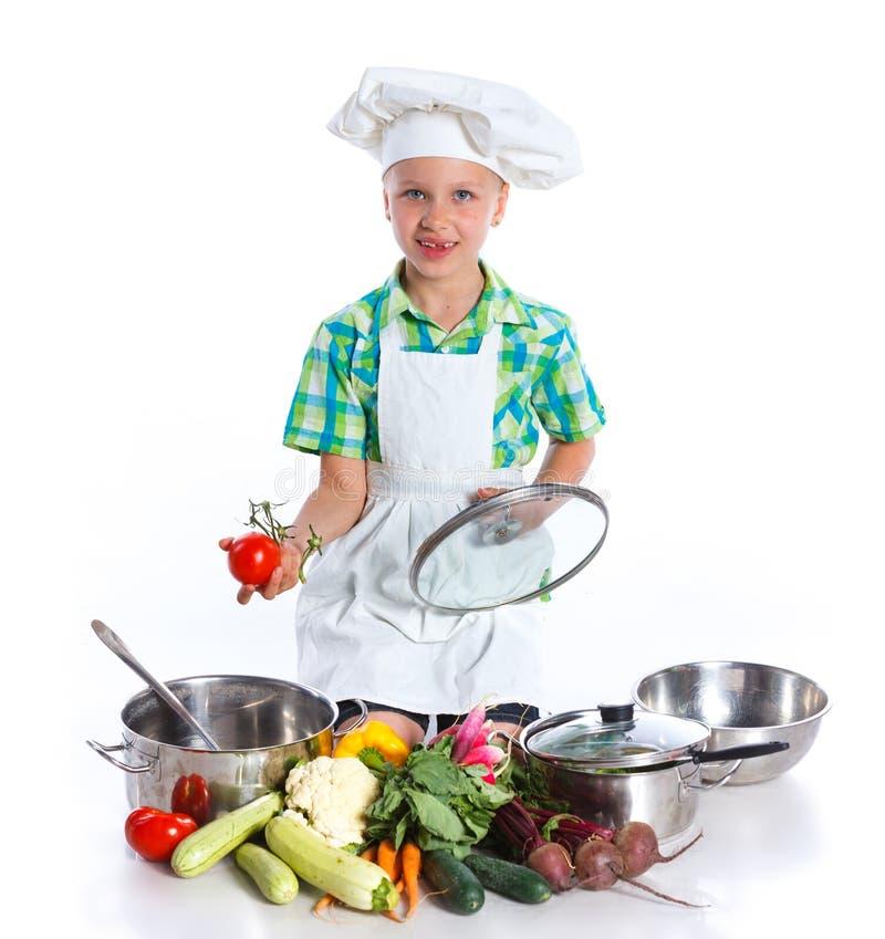 Cozinheiro do cozinheiro chefe da menina com legumes frescos fotografia de stock
