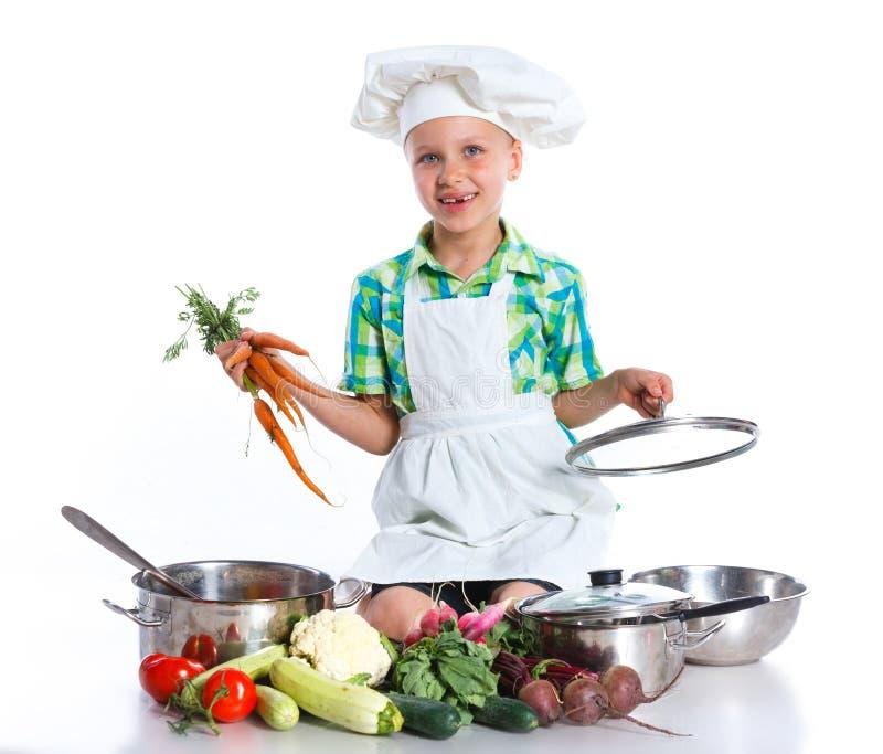 Cozinheiro do cozinheiro chefe da menina com legumes frescos imagem de stock