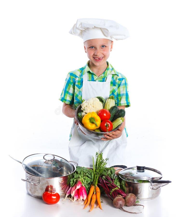 Cozinheiro do cozinheiro chefe da menina com legumes frescos imagens de stock royalty free
