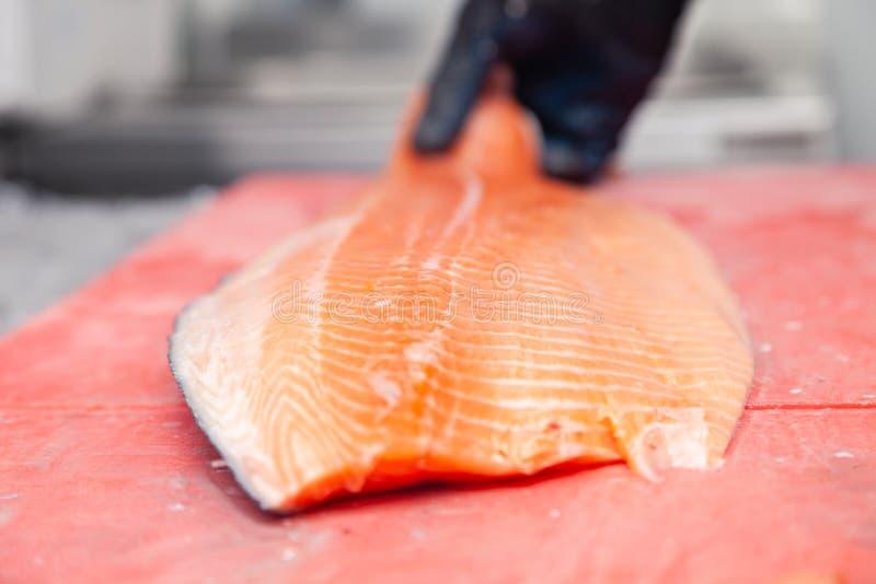 Cozinheiro do cozinheiro chefe que cinzela peixes frescos inteiros dos salmões do norueguês com a faca na placa de corte vermel fotos de stock