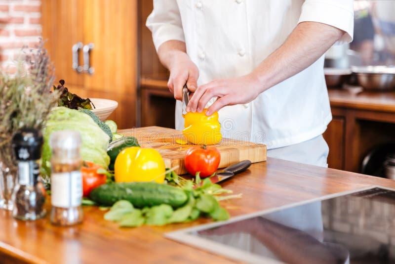 Cozinheiro do cozinheiro chefe que corta a pimenta de sino amarelo na cozinha imagem de stock royalty free