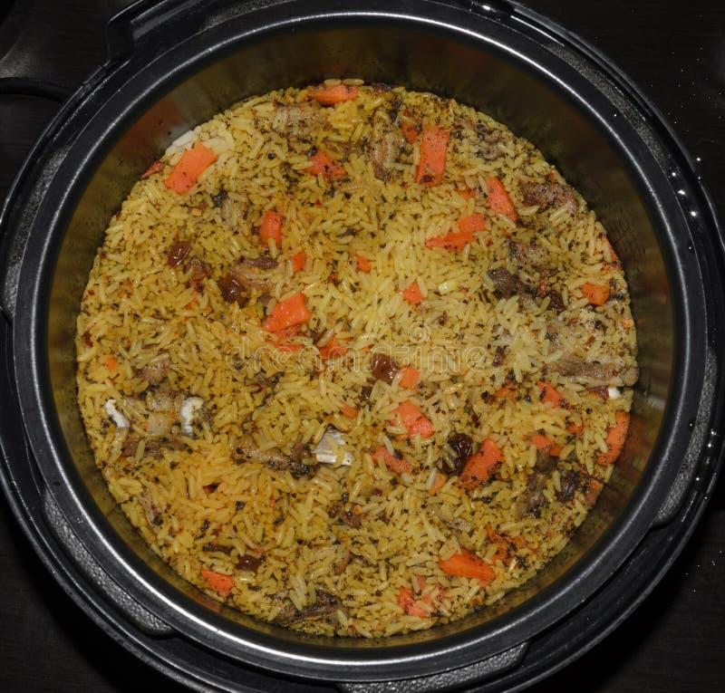 Cozinheiro do pilau em uma caçarola do arroz com cordeiro e vegetais foto de stock