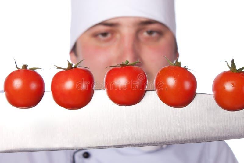 Cozinheiro dos homens. os tomates de cereja cortaram em foto de stock royalty free