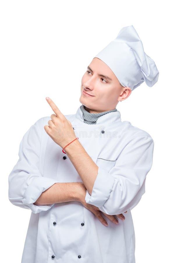 cozinheiro em pontos uniformes seu dedo em algo ao lado, retrato no fundo branco imagens de stock royalty free
