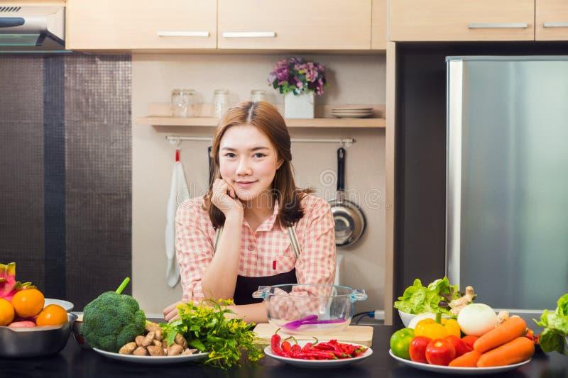 Cozinheiro fêmea asiático atrativo orgulhoso que está em sua cozinha home imagem de stock royalty free