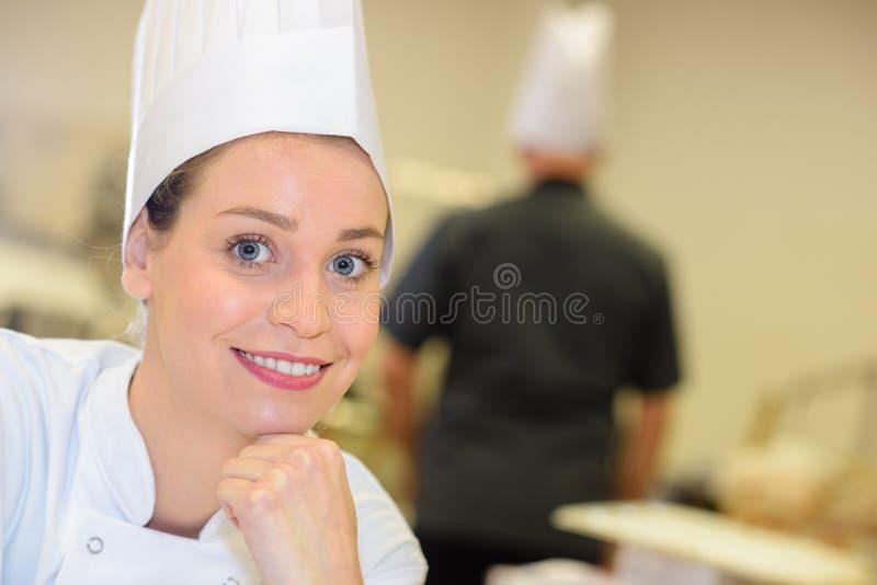 Cozinheiro fêmea de sorriso do retrato na cozinha imagens de stock royalty free
