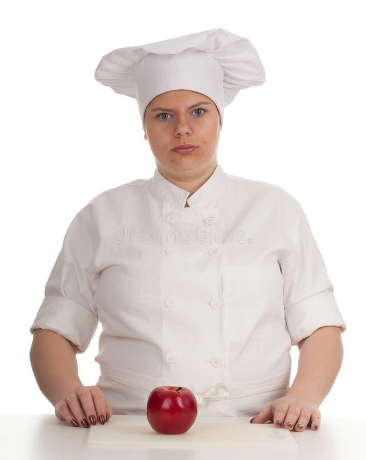 Cozinheiro fêmea gordo sério com maçã vermelha fotografia de stock royalty free