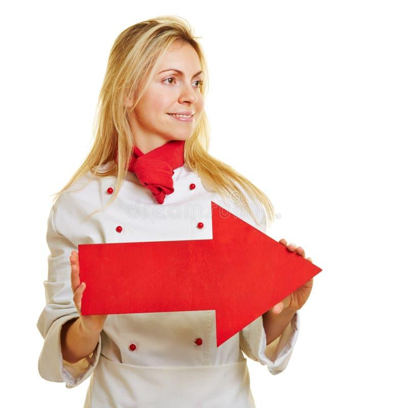 Cozinheiro fêmea no workwear com seta vermelha fotografia de stock royalty free