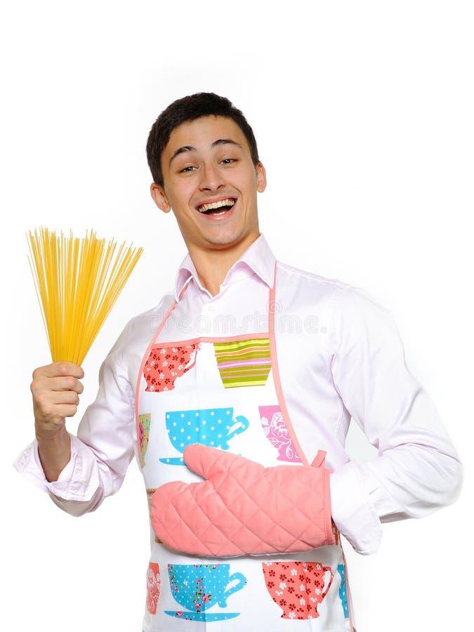 Cozinheiro feliz novo com massa do spagetti foto de stock