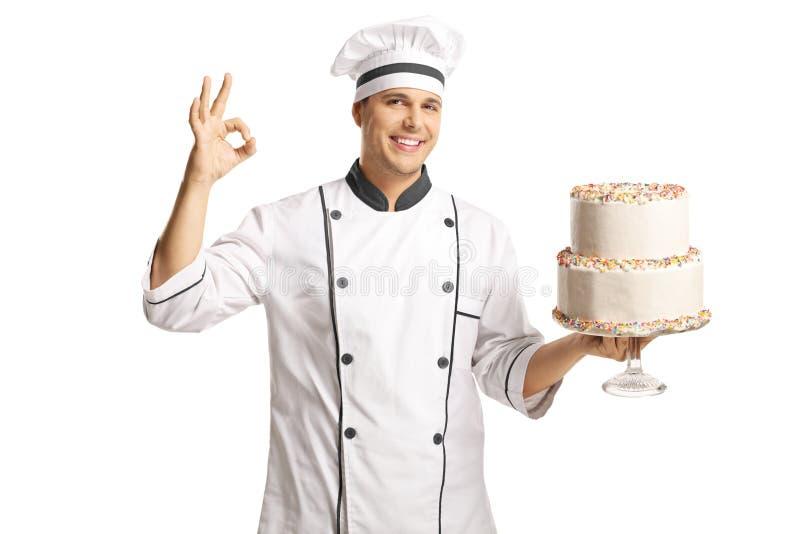 Cozinheiro masculino alegre que guarda um bolo de camada dois e que gesticula com dedos imagem de stock