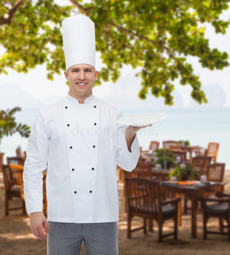Cozinheiro masculino feliz do cozinheiro chefe que mostra a placa vazia imagens de stock