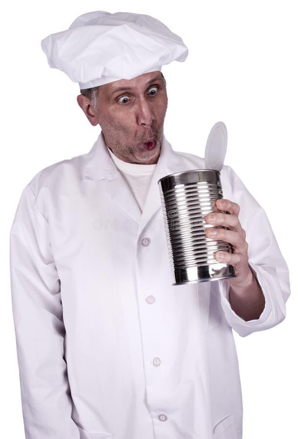Cozinheiro ou cozinheiro chefe masculino engraçado que olham na lata de estanho do alimento fotos de stock
