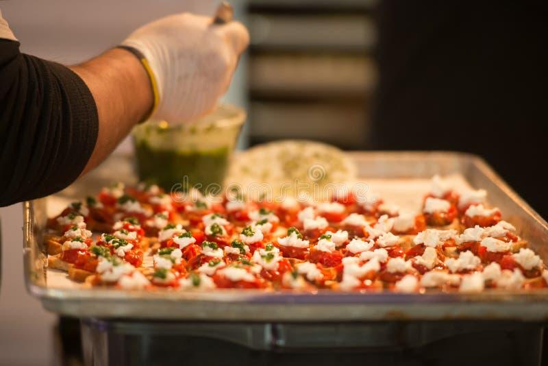 Cozinheiro principal que faz aperitivos do bruschetta com os tomates do queijo do pão e o molho do pesto imagens de stock