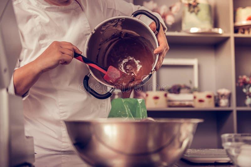 Cozinheiro profissional agradável que põe a massa no saco da pastelaria foto de stock