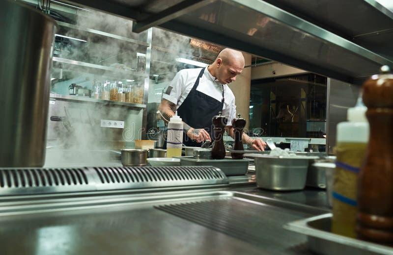 Cozinheiro profissional Cozinheiro chefe famoso no funcionamento preto do avental em uma cozinha do restaurante foto de stock