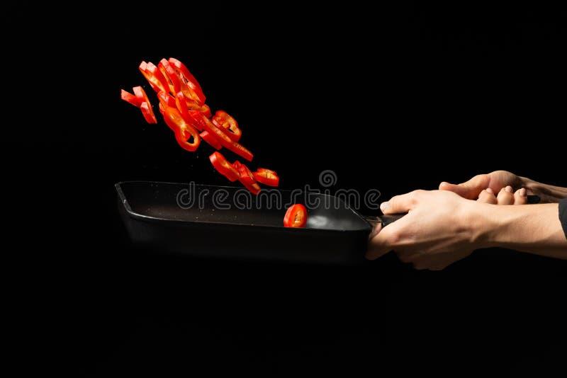 Cozinheiro profissional cozinheiro chefe que prepara o prato com pimenta doce vermelha em uma bandeja, paprika No fundo preto men imagens de stock