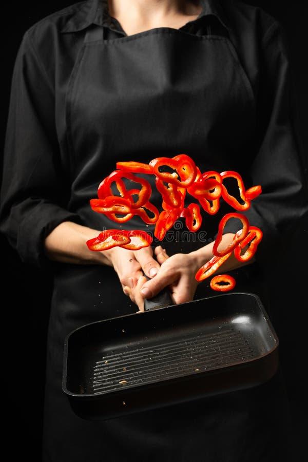 Cozinheiro profissional cozinheiro chefe que prepara o prato com pimenta doce vermelha em uma bandeja, paprika No fundo preto men imagem de stock royalty free