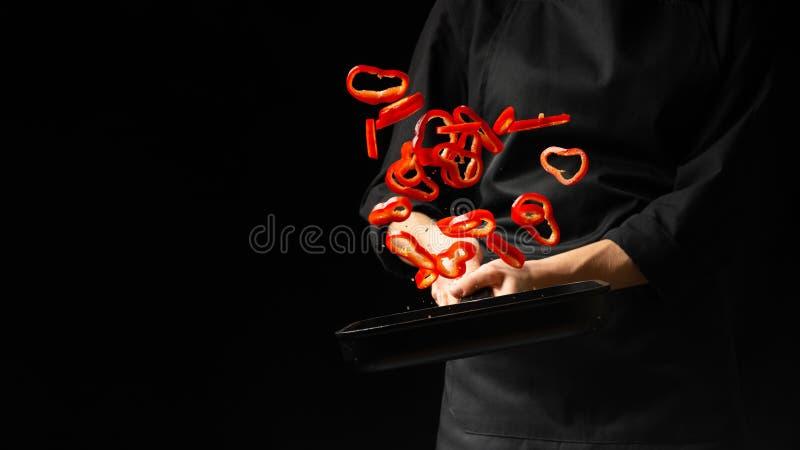 Cozinheiro profissional cozinheiro chefe que prepara o prato com pimenta doce vermelha em uma bandeja, paprika em um fundo preto  imagens de stock