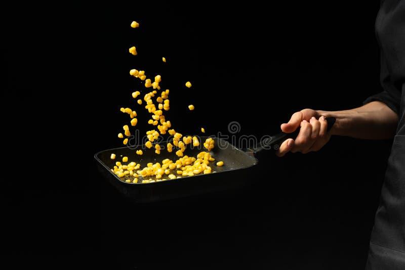 Cozinheiro profissional O cozinheiro chefe está preparando um prato com milho em uma bandeja Em um fundo preto menu, livro da rec fotos de stock