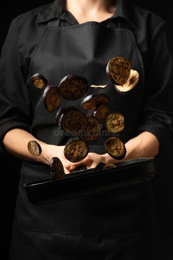Cozinheiro profissional o cozinheiro chefe prepara o prato com beringelas em uma caçarola Em um fundo preto menu, livro da receit imagem de stock