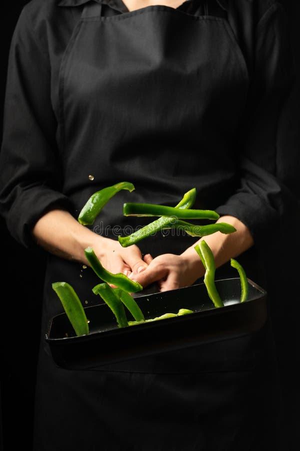 Cozinheiro profissional Prepara um prato com pimentas doces verdes em uma caçarola no fundo preto, menu, livro da receita, alimen imagens de stock