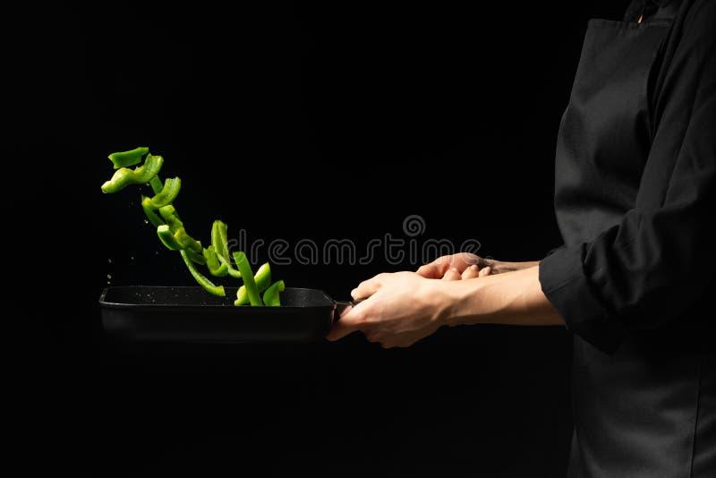 Cozinheiro profissional Prepara um prato com pimentas doces verdes em uma caçarola no fundo preto, menu, livro da receita, alimen foto de stock